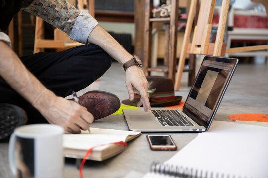 Male artist planning at laptop on floor in art studio