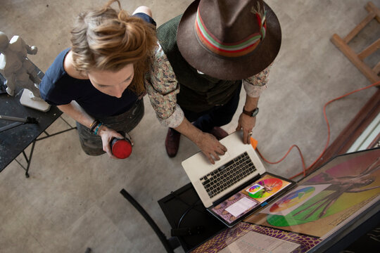 Artists working at laptop and monitor in art studio