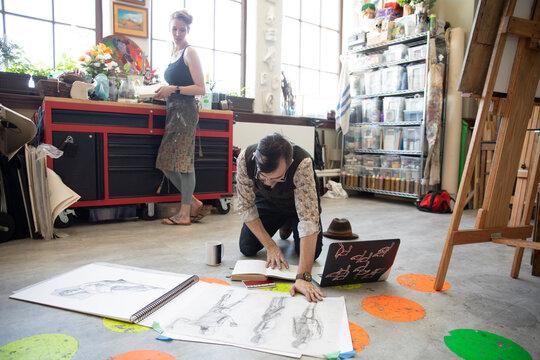Male artist reviewing sketches on floor in art studio