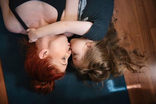 Affectionate mother kissing daughter on yoga mat