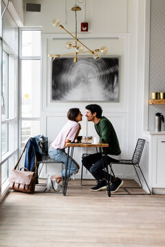 Affectionate young couple at cafe table