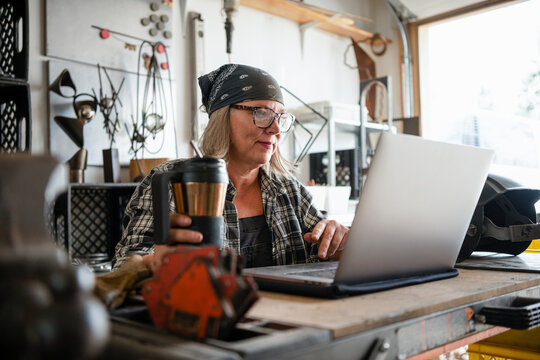 Female sculptor with coffee working at laptop in workshop garage