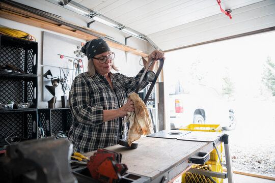 Female sculptor assembling sculpture in workshop garage