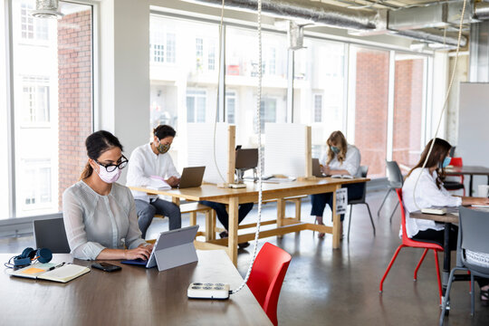 Coworkers in face masks in socially distanced coworking space