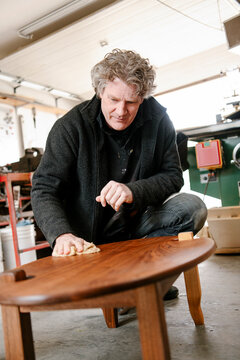 Male carpenter finishing coffee table in garage workshop