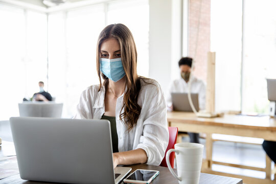 Woman and coworkers in face masks in socially distanced cowork space
