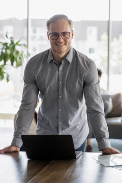 Portrait of man standing at desk smiling in coworking space