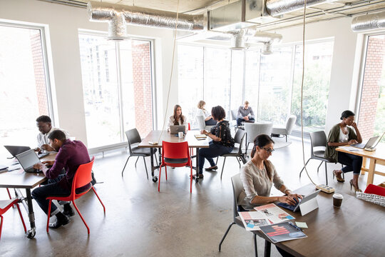 Businesspeople working in socially distanced coworking space