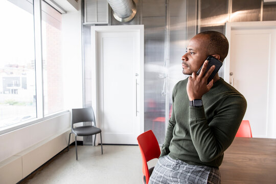 Businessman standing using phone in coworking space
