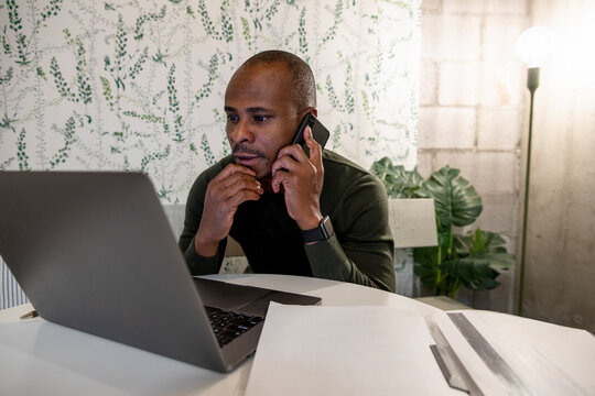 Close up of man discussing work on laptop on phone