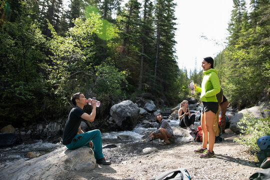 Young hikers resting and drinking water at sunny stream in woods