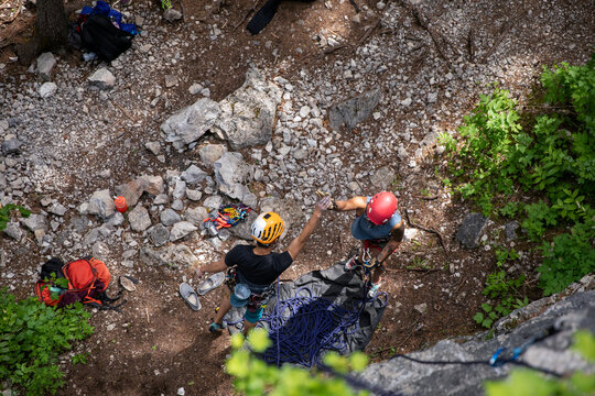 Young rock climbers in helmets high fiving
