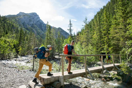 Young male friends hiking on sunny footbridge over stream in woods