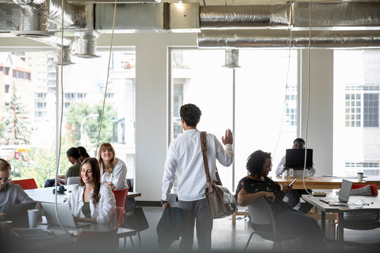 Businessman with briefcase waving to coworkers in coworking space