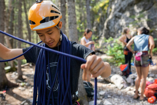Young male rock climber preparing equipment