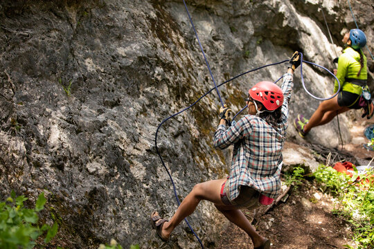 Young woman rock with safety rope rock climbing