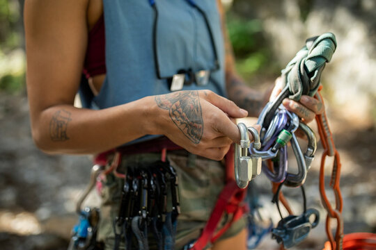 Close up young female rock climber with tattoos preparing equipment