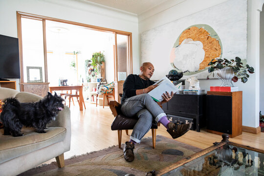 Man reading book on chair relaxing with pet dog