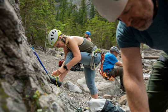 Female rock climber tying shoelace at rock