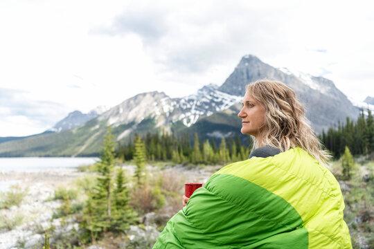 Serene woman in camping sleeping bag enjoying coffee and mountain view