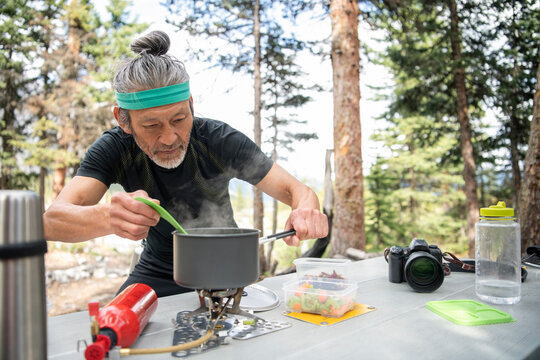 Man cooking on camping stove at picnic table