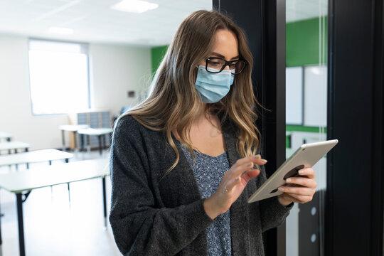 Teacher wearing mask using tablet