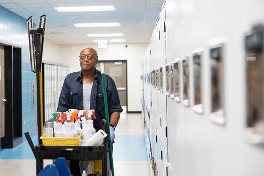 Cleaner pushing trolley in school corridor