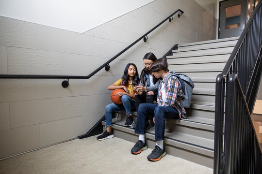 Students sitting on staircase at school