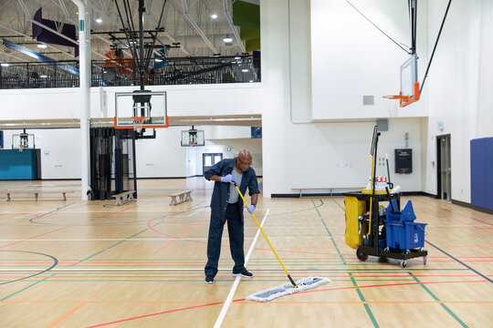 Cleaner working in school gymnasium