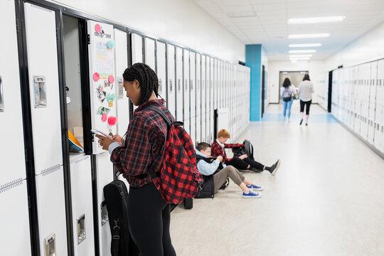Student using phone by school locker