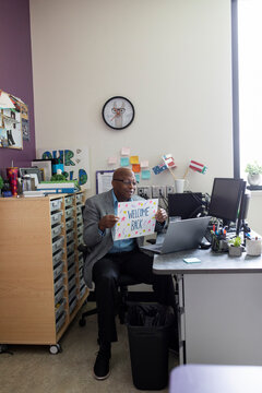 Teacher holding welcome back sign up to laptop