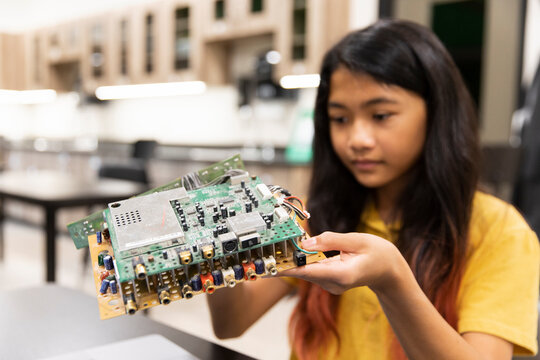 Student examining circuit board in IT class