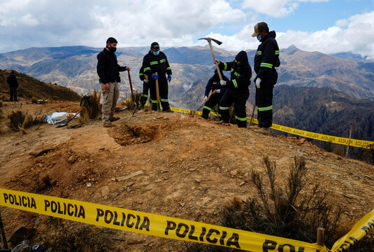 Police officers of the Special Force to Combat Crime (FELCC) dig as they investigate several clandestine graves in Palca