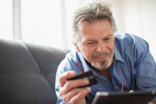 Senior man with headphones and credit card using digital tablet on sofa