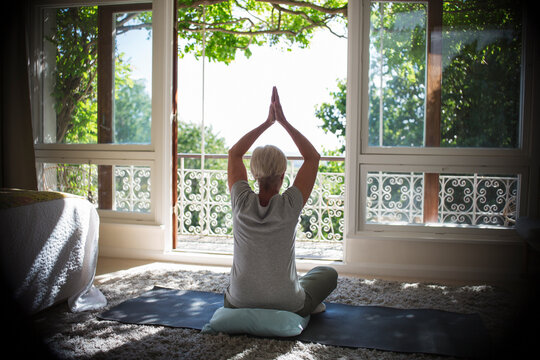 Serene senior woman practicing yoga at sunny tranquil balcony doorway