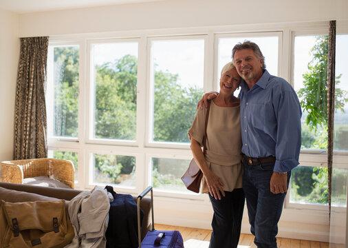 Portrait happy senior couple arriving at house rental