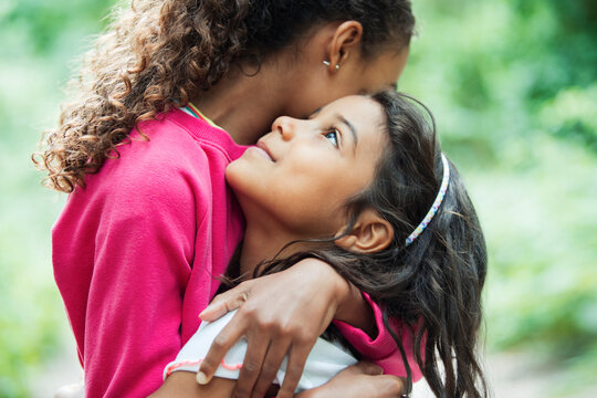 Close up affectionate cute sisters hugging