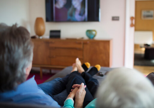 Senior couple holding hands and watching TV on living room sofa