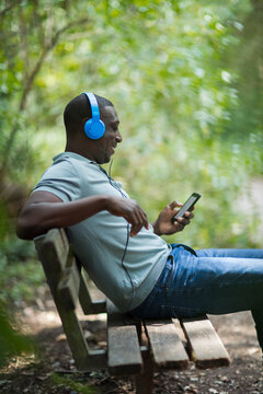 Man listening to music with headphones and smart phone on park bench