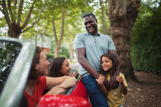 Happy family laughing at convertible in driveway