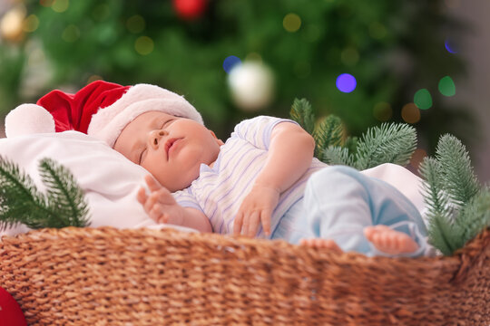 Cute little baby sleeping in basket at home on Christmas eve