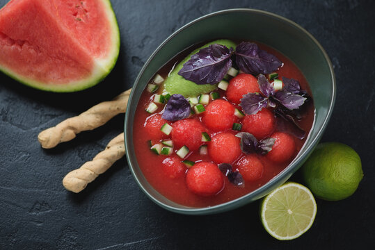 Bowl of watermelon and tomato gazpacho soup served with grissini, studio shot on a black stone background, elevated view