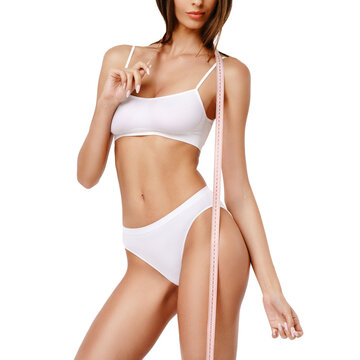 Slim tanned woman's body over gray background - waist measurement