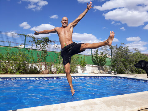 Happy man on vacation is jumping into pool.