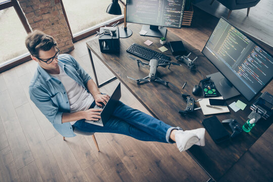 Top above high angle view of his he nice attractive focused skilled guy geek typing coding web development remote support security safety at modern loft industrial home office work place station