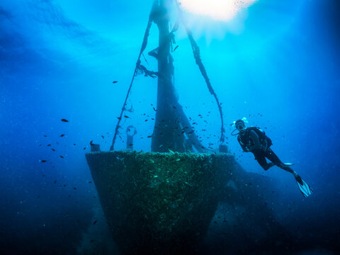 A scuba diver in front of a sunken shipwreck on the Aegean seabed in Skiathos, Greece