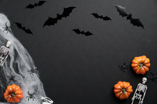 Happy halloween holiday concept. Bats silhouettes, pumpkins, spider web, skeletons, spiders on black background. Halloween card.
