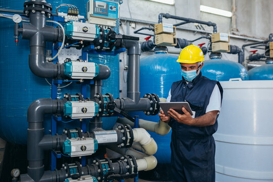 industry worker checking chemical water treatment equipment