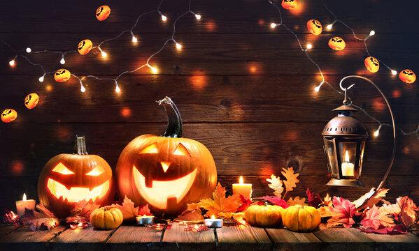 Halloween pumpkins with lantern on wooden background
