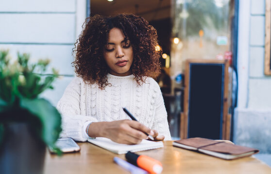 Beautiful dark skinned woman sitting at table on cafe terrace doing homework and research for learning, serious african american female journalist concentrated on making notes and writing article